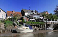 Sportboote bei Ebbe in der Este trockengefallen - die Boote liegen am Ufer von Hamburg Cranz im Schlick.