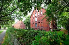 Ziegelgebäude zwischen Bäumen - ehem. Polizeigebäude, jetzt zu Wohnzwecken umgewidmet - Fotos aus Hamburg Neuland.