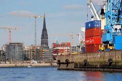 Blick aus dem Hansahafen über die Norderelbe zu den Baustellen am Grasbrookhafen der Hamburger Hafencity. Container am Kai - Turm der Nikolaikirche (2007)