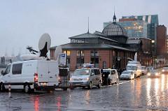 Fernsehteams haben mit ihren Übertragungswagen nach einer Sturmflutwarnung mit ihren Übertragungswagen Position am Altonaer Fischmarkt bezogen und warten auf das übertragungsfähige Hochwasser.