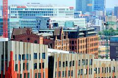 Fassade moderner Architektur und historische Ziegelgebäude in der Hafencity Hamburg - im Hintergrund das Spiegelgebäude auf der Ericusspitze.