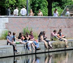 Uferpromenade am Mittelkanal im Hamburger Stadteil Hammerbrook - Menschen sitzen in der Sonne am Wasser.