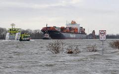 Die Uferbefestigung bei Hamburg Othmarschen ist überspült; Gebüsch ragt aus dem Wasser; ein Containerschiff läuft mit Schlepperhilfe den Hamburger Hafen an - eine Hafenfähre fährt Richtung Finkenwerder.