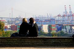 Liebespaar im Rosengarten an der Elbchaussee - Blick auf die Hafenanlagen, Container und Containerbrücken im Hamburger Hafen.