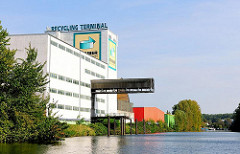 Industriegebäude am Ufer des Billbrookkanals in Hamburg Billbrook - eine Krananlage führt über das Wasser, so dass Schiffe entladen werden können.