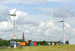 Gewerbegebiet Hamburg Altenwerder, geparkte Lastkraftwagen mit Containern beladen - Windkraftanlagen mit riesigen Rotorblättern - dazwischen der Kirchturm der St. Gertrudkirche.