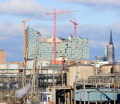 Erdölraffinerie im Hamburger Hafen - Kleiner Grasbrook - im Hintergrund die Baustelle der Elbphilharmonie mit Baukränen und der eingerüstete Kirchtumr der Nikolaikirche.