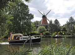 Reitbrooker Mühle am Ufer der Dove-Elbe - Windmühle mit Flügeln in Hamburg - Schilf am Flussufer - Motorboot in Fahrt.