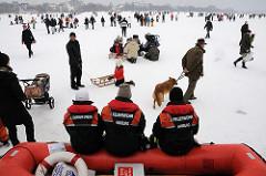 Rettungskräfte sitzen am Alsterufer und beobachten das Treiben auf dem Eis. Wenn jemand in die Eisdecke einbricht werden sie mit ihrem Schlauchboot zur Stelle sein und helfen.