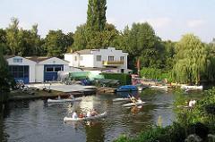 Kanus auf dem Winterhuder Goldbekkanal - Gebäude einer Bootslagerung und Kanuvermietung am Ufer des Hamburger Kanals.