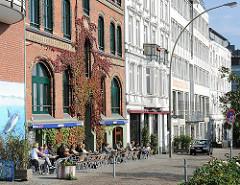Strassencafe in der Sonne - Weinlaub an der Ziegelfassade eines ehem. Hafenbetriebes in Hamburg St. Pauli.