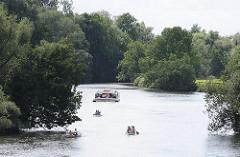Die Ufer der Dove-Elbe sind teilweise dicht mit Bäumen bewachsen; Kanus fahren auf dem ruhigen Wasser, eine Barkasse fährt langsam flussabwärts.