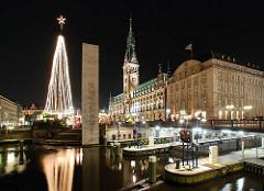 Nachtaufnahme von Hamburg - Blick über die Schleusenbrücke zum Rathaus Hamburg  - ein beleuchteter Weihnachtsbaum steht auf dem Rathausmarkt.