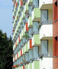 Balkons eine mehrstöckigen Wohnhauses in Hamburg Lohbrügge. Balkonkästen mit blühenden Blumen.