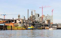 Industrieanlage im Steinwerder Hafen - eine Barkasse der Hafenrundfahrt fährt durch das Hafenbecken - im Hintergrund die Baustelle der Elbphilharmonie.