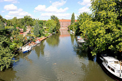 Blick über den Verbindungskanal / Rückertkanal zum Mittelkanal - Sportboote liegen am Ufer der Kleingärten in Hamburg Hamm.