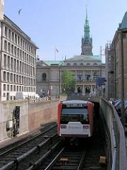 Einfahrt der U-Bahn in den Tunnel zum Rathaus - im Hintergrund die Hamburger Börse und der Turm des Rathauses.