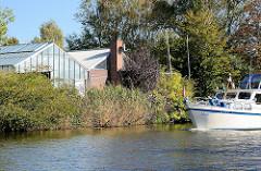Treibhäuser, Glashäuser am Ufer der Dove Elbe in den Vierlanden, Stadtteil Curslack - Bezirk Hamburg Bergedorf; ein Sportboot in Fahrt.