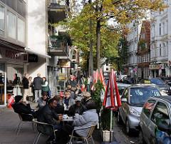 Leben und Wohnen in Hamburg - Strassencafe in der Langen Reihe in Hamburg St. Georg; parkende Autos / Strassenverkehr.