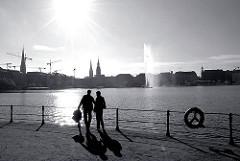 Blick von der Promenade an der Lombardsbrücke über die Binnenalster - ein Paar steht in der Sonne an der Alster.