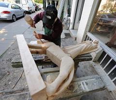 Arbeit an einer Skulptur mit Engelsfigur auf der Strasse vor der Holzwerkstatt der Kanzleistrasse.