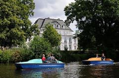 Tretboote am Alsterufer - weisse Villa zwischen Bäumen.