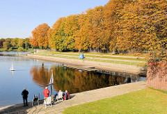 Freibad Stadtparksee im Herbst - Kastanienbäume mit rötlich braunem Herbstlaub - Segelboote / Modellboote fahren auf dem Wasser.