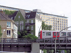 U-Bahnbrücke Hoheluft - ein Hochbahnzug fährt in den Bahnhof ein - im Hintergrund ein Hochhaus am Grindelberg.