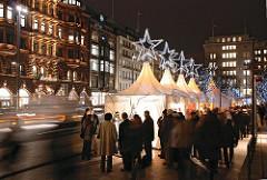 Weihnachtsmarkt in Hamburg - Weihnachtsdekoration auf dem Hamburger Jungfernstieg - beleuchtete Zelte mit Stern auf der Spitze - Marktbesucher und Strassenverkehr.