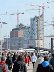 Spaziergänger_innen an der Überseebrücke; Baustelle der Elbphilharmonie und Bürogebäude am Kehrwieder der Hamburger Hafencity.
