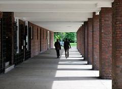 Fussweg an der Eiffestrasse in Hamburg Hamm - Säulen aus Ziegelsteinen; Fussgänger gehen im Säulengang.
