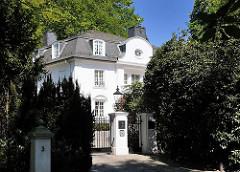 Wohnen in Hamburg Osdorf - Villa hinter hohen Rhododendronpflanzen als Sichtschutz. Architekturfotos aus Hamburg.