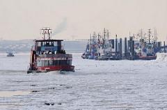 Hafenfähre auf der eisbedeckten Elbe - im Hintergrund die Schlepper am Anleger in Hamburg Neumühlen.