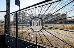 Eingangstor der GEG - im Hintergrund ein Teil der alten Fabrikgebäude. Die historische Industriearchitektur Hamburgs - alte GEG Großeinkaufs-Gesellschaft Deutscher Consumvereine Gebäude auf der Veddel. Der Fabrikkomplex  stellt ein Denkmal der Arbeit