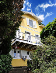 Einzelhaus mit gelber Fassade und Balkon im Blankeneser Treppenviertel.