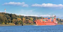 Der Containerfeeder LAURA ANN auf der Elbe vor Hamburg Nienstedten - am Elbhang Herbstbäume bis herunter zum Elbufer. Rotes Frachtschiff mit Containerfracht, blauer Himmel weisse Wolken.