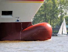 Wulstbug eines Containerfeeders auf der Elbe im Hamburger Hafen - ein Segelschiff fährt am Rand der Elbe.