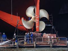 Werftarbeiter auf einem Schwimmdock am Steuerruder eines Frachtschiffs - Werftarbeit auf Hamburg Steinwerder.