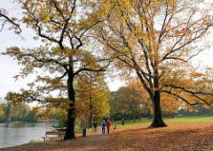 SpaziergängerInnen in der Herbstsonne im Harvestehuder Eichenpark an der Alster.
