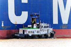 Der Lotse geht an Bord des Containerschiffs; das Lotsenschiff hält an der Bordwand die Fahrt des Frachters.