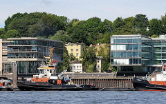 Elbufer von Hamburg Ottensen - Hafenschlepper an ihrem Liegeplatz von Neumühlen - Bürohäuser am Wasser - historische Wohnbebauung an der Elbtreppe im Hintergrund.