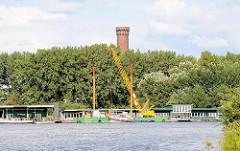 Blick über die Norderelbe zum Ponton des ehem. Zollanlegers in Hamburg Entenwerder - dahinter die Bäume vom Elbpark in Rothenbursort und die Spitze des Wasserturms.