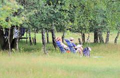 Entspannung am Boberger See - ein Paar hat seine Badeanzüge zum Trocken aufgehängt - sie sitzen in Campingstühlen und lesen.
