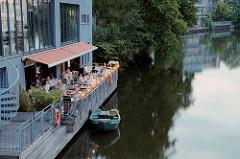 Abendstimmung auf einer Terrasse am Osterbekkanal - ein Ruderboot liegt an der Kaimauer.