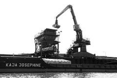 Ein Bagger löscht eine Ladung Schüttgut von dem Binnenschiff Kaja Josephine - Güterumschlag am Kai des Müggenburger Kanals in Hamburg Veddel.