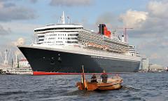 Die Queen Mary 2 hat eine Länge von 345m und eine Breite von 41m; das Passagierschiff hat eine Besatzung von 1253 und kann ca. 3000 Passagiere an Bord nehmen.