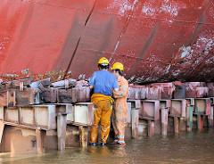 Werftarbeiter im Trockendock; ein Schiff ist eingedockt; der Kiel wird mit Pallen abgestützt und in Position gehalten.