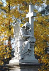 Trauernder Engel / Trauerengel auf einem Grabstein des Friedhofs St. Johannis Kirche in Hamburg Neuengammme. Herbstlaub im Hintergrund.