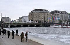 Blick vom Ballindamm auf die Promenade an der Binnenalster und zur Reesendammbrücke und den Geschäftshäusern am Jungfernstieg in Hamburg-Neustadt.