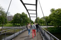 Spaziergänger auf der Fussgängerbrücke Heinz-Gärtner-Brücke über den Osterbekkanal - im Hintergrund der Johannes Prassek Park und Gebäude der Alstercity in Hamburg Barmbek Süd.